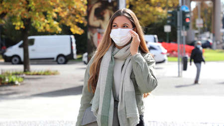 Woman wearing medical face mask. Girl adjusts the mask in city street.