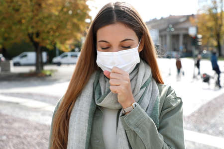 COVID-19 Young woman coughs with surgical mask during coronavirus pandemic disease in city street. Girl having symptoms like coughing and headache.