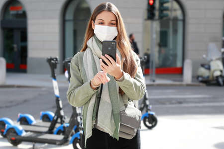 Young woman with protective mask downloads the app to use the electric scooter in city street Standard-Bild