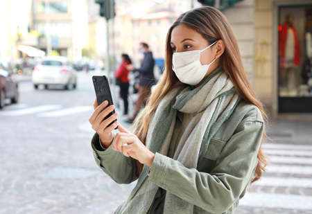 Happy young woman in surgical mask for protection against the virus stands on city street makes video call