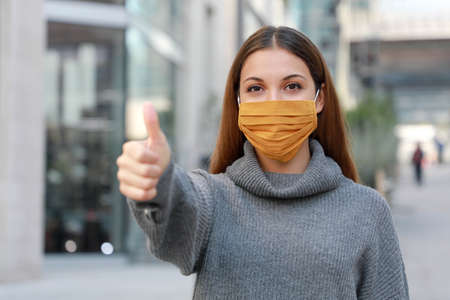 Use the mask! Young woman wearing protective mask showing thumbs up in city street.