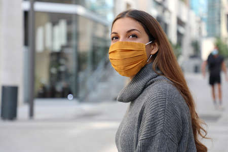 Young woman with protective mask looks around in modern city street Standard-Bild