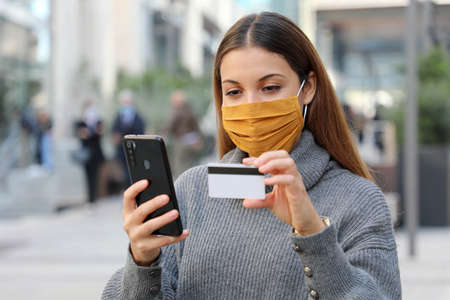 Portrait of young beautiful woman wearing protective mask chill out and make payment through credit card and smartphone app in the street