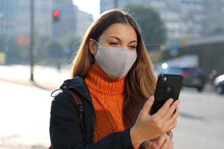Young business woman with protective mask checking email on mobile phone waiting for a taxi on street in the morning Standard-Bild