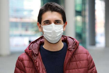 Portrait of worried man in modern city street wearing protective face mask Standard-Bild