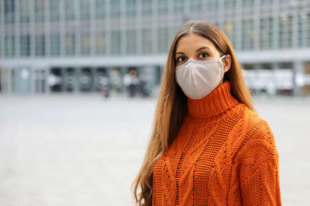 Portrait of a young business woman wearing protective mask standing on the street looking in front of her worried. Copy space.