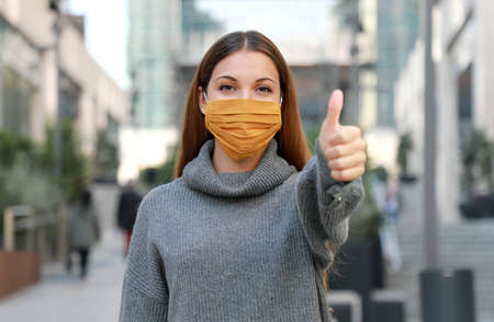 Use the mask! Young woman wearing protective face mask showing thumbs up with modern city street on the background.