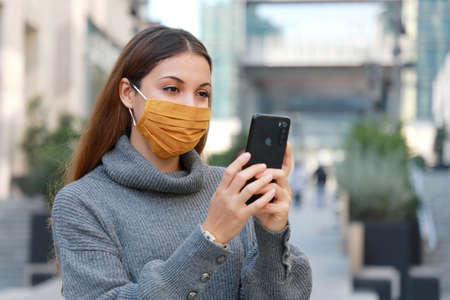 Portrait of young woman standing on street in protective mask and messaging with smartphone