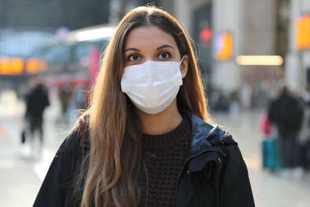 Portrait of young woman wearing surgical mask at train station Standard-Bild