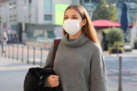 Portrait of a young student woman with surgical mask walking in city street