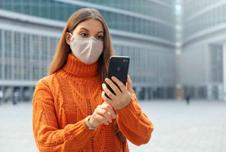 Young woman wearing face mask using smartphone app in modern city street. Copy space.