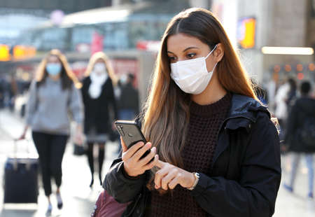 University student commuter walking using mobile phone wearing face mask protection as prevention for coronavirus in city airport or station