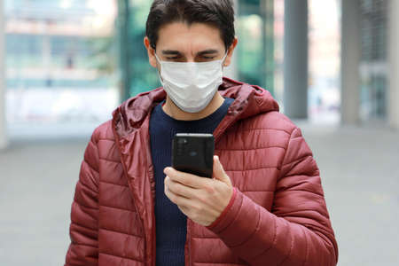 Young caucasian man with protective mask reading news or message on smartphone in modern city street Standard-Bild