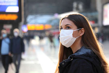 Close up of traveler woman wearing surgical mask at the airport. Worried young woman looking timetables of departures arrivals waiting information for her flight. Standard-Bild