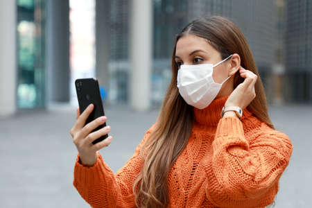 Video calling and Social Distancing. Beautiful young woman in city street wearing protective mask using mobile phone to make video calling or video conference outdoor. Standard-Bild