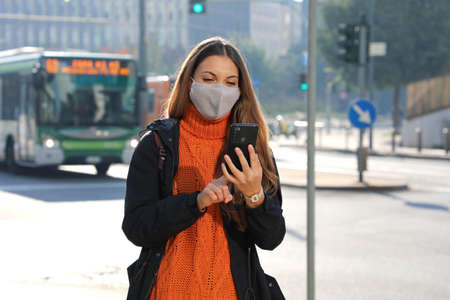 Young business woman with protective mask checking chat messaging on smartphone app waiting for a bus on street in the morning