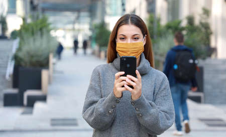 Young woman with fabric mask messaging with mobile phone while walking in pedestrian street. Copy space. Standard-Bild