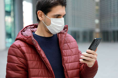 COVID-19 Portrait of young man wearing protective mask reading news on smartphone app in modern city street Standard-Bild
