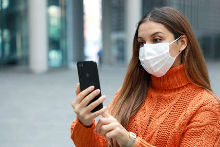 Video calling and Social Distancing. Beautiful young woman in city street wearing protective mask using mobile phone to make video calling outdoor. Copy space. Standard-Bild