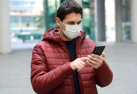 Man wearing surgical mask using smartphone app in modern city