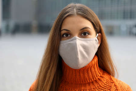 Close up of girl wearing face mask posing in the street looking at camera