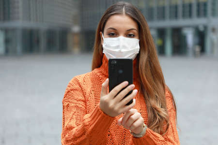 Young business woman with surgical mask holding smartphone while walking in modern city