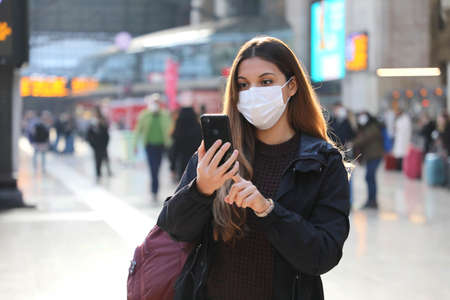 Student girl wearing protective mask buying ticket online with smartphone app at train station