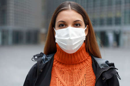 Close up of young woman in medical mask standing in empty modern city street looking at camera ready for vaccination campaign