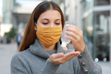 Close up of young woman with protective mask using alcohol gel sanitizer hands in modern city street Standard-Bild