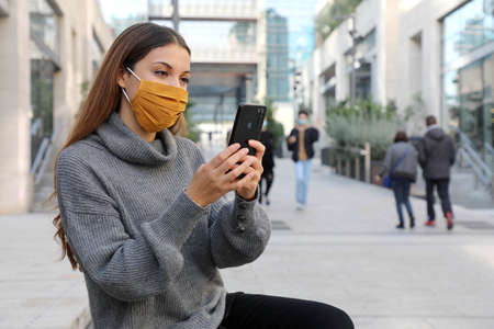 Attractive young business woman with face mask sitting on bench of pedestrian city street using a smartphone