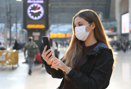 Business woman wearing protective mask buying ticket online with smartphone app at train station Standard-Bild