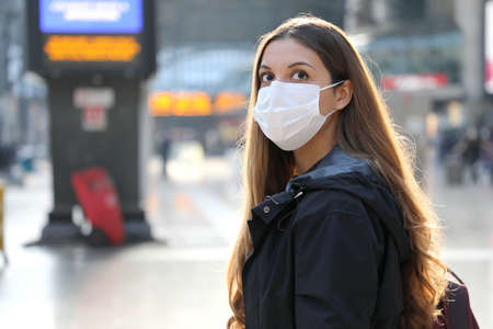 Portrait of traveler woman wearing surgical mask at train station looking worried in front of her. Copy space.