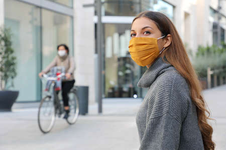 Confident young woman with protective mask looks around sitting on bench waiting for better times in modern city