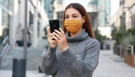 Portrait of young woman standing on street wearing protective mask and messaging with smartphone Standard-Bild
