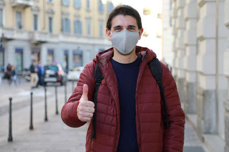 Portrait of optimistic young man wearing protective mask showing thumbs up in city street