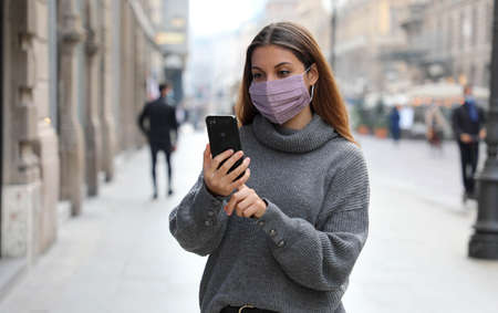 Business woman typing on smart phone in city street wearing face mask protection Standard-Bild