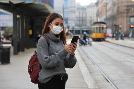 Portrait of stylish woman waiting tram with protective face mask buying ticket online with smartphone on street