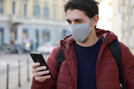 Happy young man with protective mask looks his smartphone in street. Student guy with face mask using mobile phone outdoors.