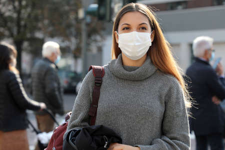 Portrait of young student woman walking in city street wearing surgical mask. Girl with face mask walks on road and people respecting social distancing stopped at the traffic lights on background. Standard-Bild