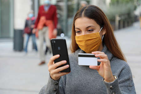 Young business woman wearing protective mask with credit card and smartphone purchasing outdoor. Successful woman with face mask is using mobile phone and bank card for online shopping in city street. Standard-Bild