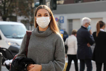 Portrait of young student woman walking in city street wearing surgical mask. Girl with face mask walks on road with people and traffic cars on the background.