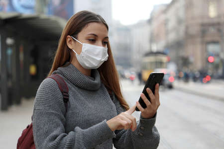 Student teenager girl with protective mask paying for online transport ticket via banking application on smartphone in city street Standard-Bild