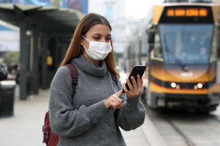 Young woman with protective mask buying and paying for online transport ticket via banking application on smartphone in city street
