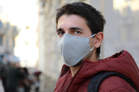 Close up of man in protective mask outdoors. Young man stands in street and looking at camera.