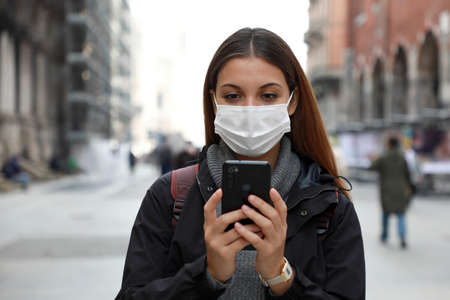 Close up of young university student woman wearing surgical mask using her mobile phone in city street
