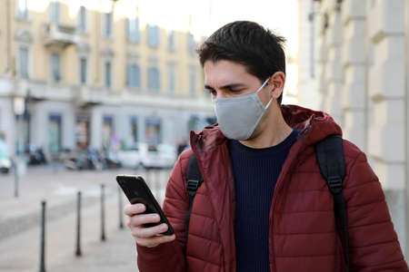 Caucasian man wearing face mask using mobile phone when walking in city street