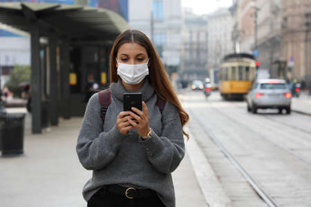 Pretty young woman with protective mask buying and paying for online transport ticket via banking application on smartphone walking in city street