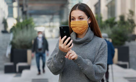 Portrait of young woman with protective mask video calling with someone while walking in city street