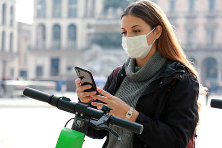 New eco-friendly transport. Young business woman with surgical mask unlocks e-scooter with her mobile phone. Woman uses an app on her smartphone to unlock a shared electric scooter on a city street. Standard-Bild