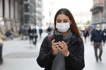 Beautiful university student woman wearing surgical mask using her mobile phone while walking in the street Standard-Bild